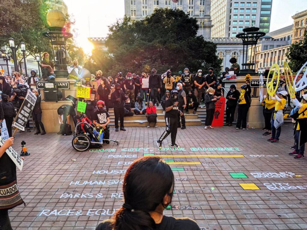 A group of protestors in Oscar Grant Plaza stand around a painting on the ground. The painting contains bar graphs of the Oakland People's Budget compared with the 2021 City Budget.